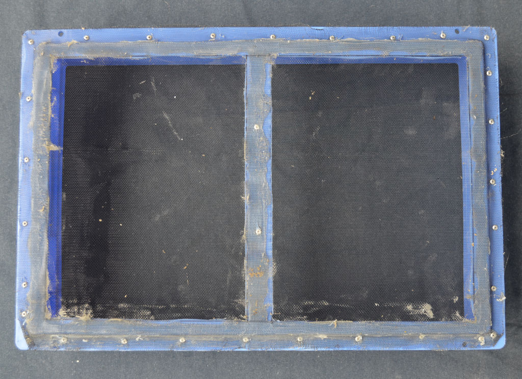 Close up of the bottom of a mealworm tray using the screen method. Two sections have been cut out of the bottom of the tray and aluminium screen is siliconed and riveted to the bottom.