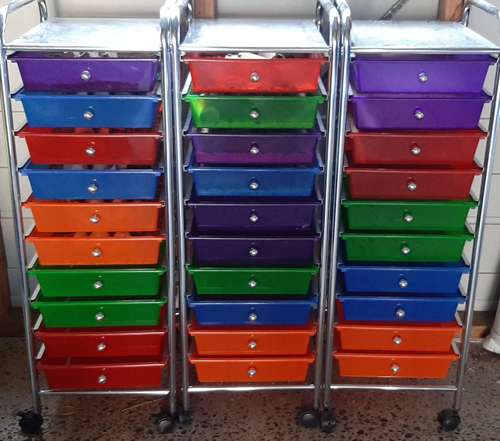 Photo of a prefabricated or bought tray system. Comprises of three separate units next to each other. Each unit has a shiny metal frame with colored pull out trays. Trays are multiple colors.