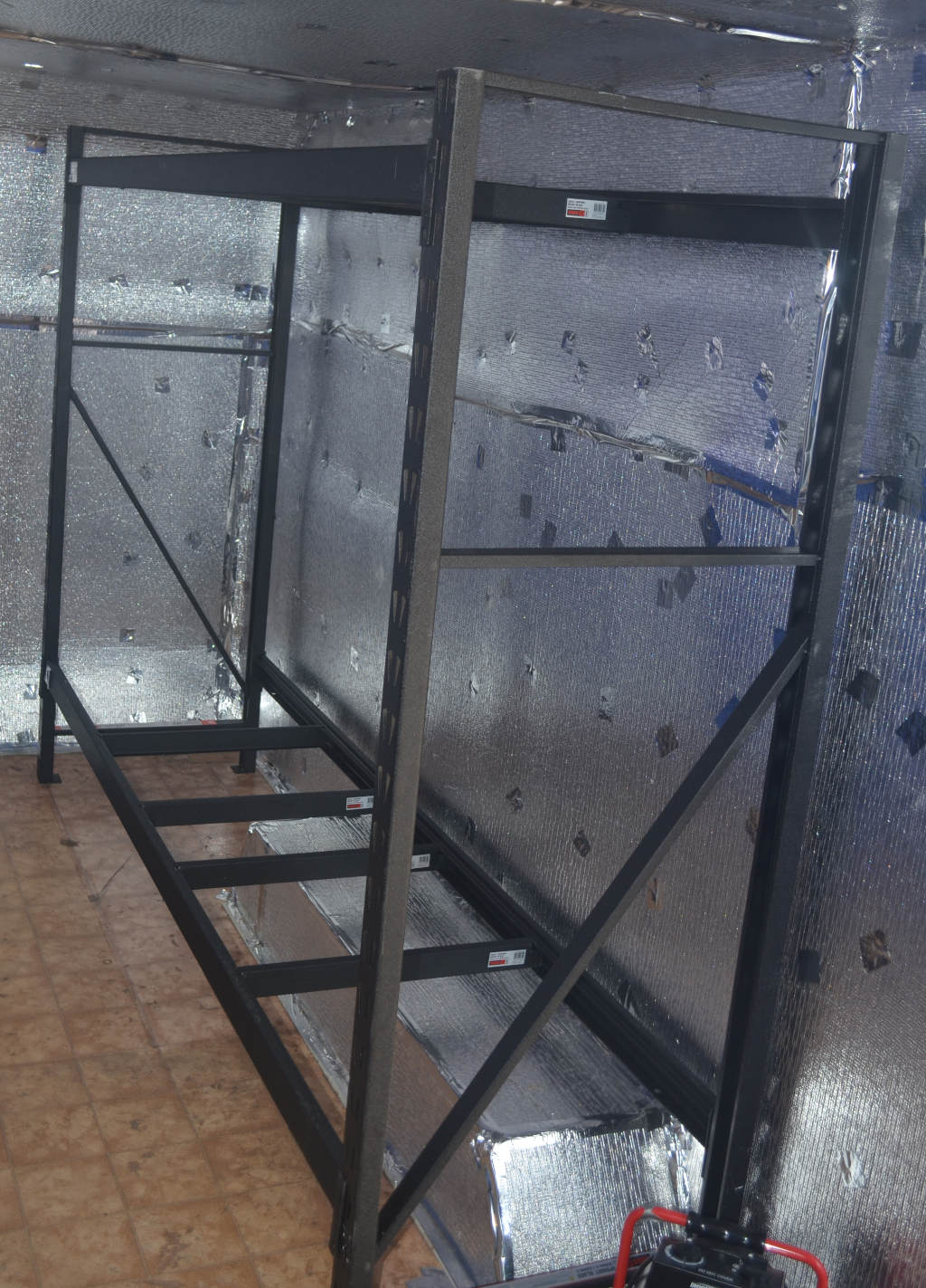 photo of a black metal frame used to make a commercial mealworm shelving. The frame sits inside a commercial insect farm with aluminium insulation on walls.
