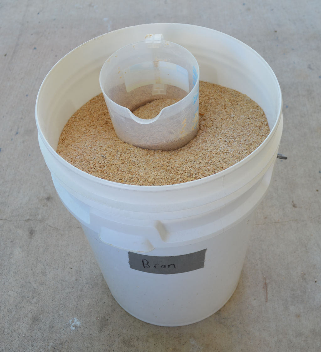 Photo of a 20 liter white bucket of wheat bran for commercial mealworm breeding. A measuring jug is at the top of the wheat bran to measure out bran.