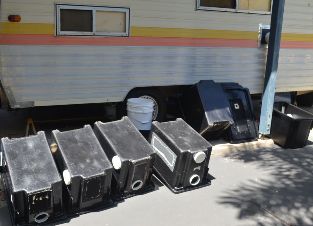 Photo of black cricket containers drying against the outside of a caravan insect farm.
