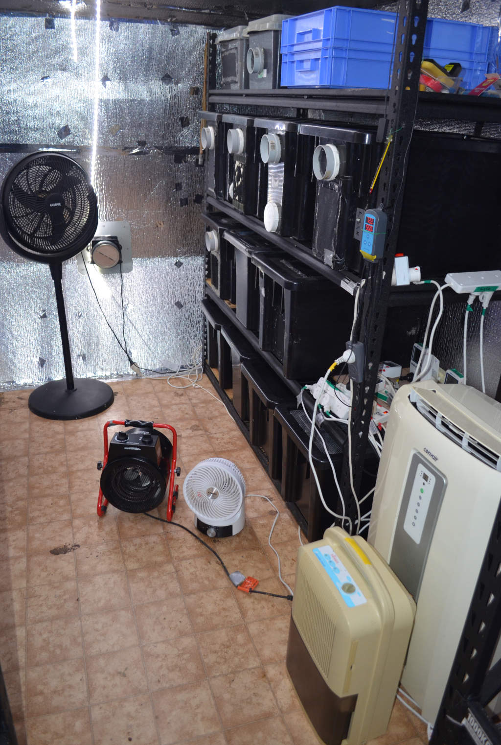 Photo of climate control equipment for a cricket farm. Includes black pedestal fan, black radiant heater, white 360 degree fan, cream air conditioner and dehumidifier.